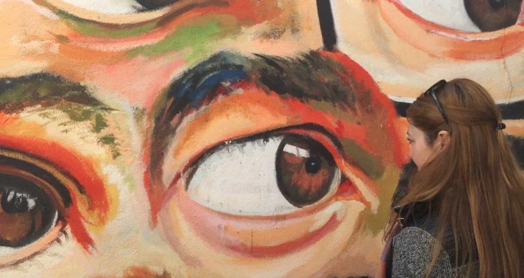 Olga blickt auf das Graffiti-Bild mit Augen, die auf sie zurückstarren
