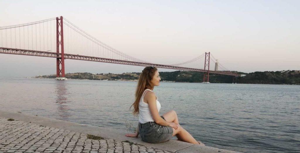 Olga sitzt am Tagus Fluss mit der Sicht auf die rote Lissabon Brücke des 25. Aprils
